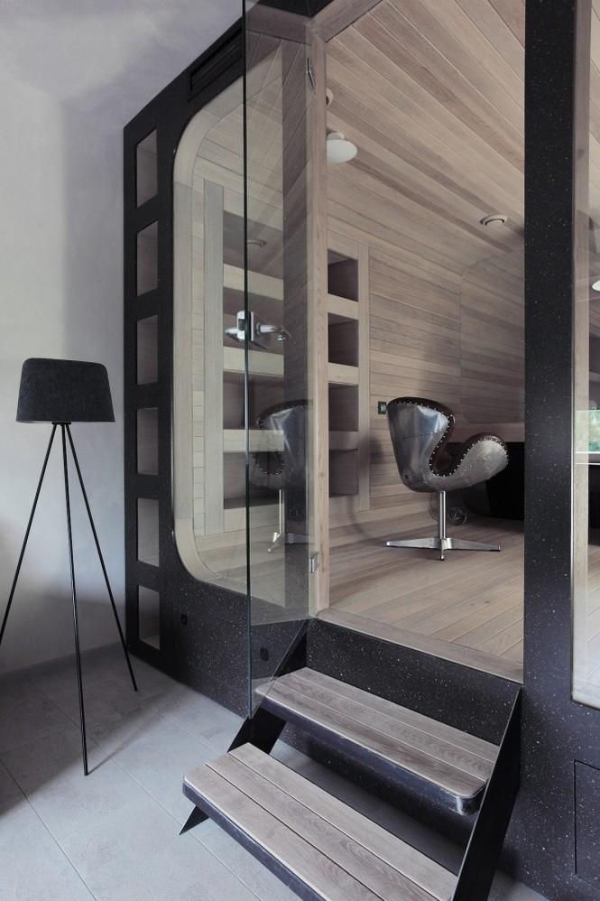 Квартира по проекту Петра Костёлова с округлыми стенами, обшитыми дубом, и сквозным пространством во всю ширину квартиры.